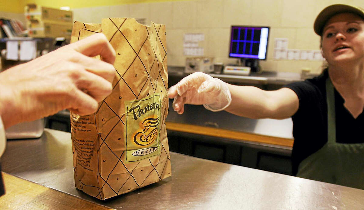 An employee passes an order to a customer at the Panera store in Brookline, Mass.