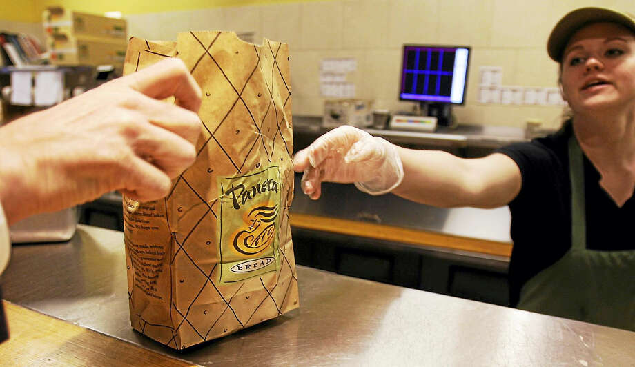 An employee passes an order to a customer at the Panera store in Brookline, Mass. Photo: The Associated Press File Photo / AP2010