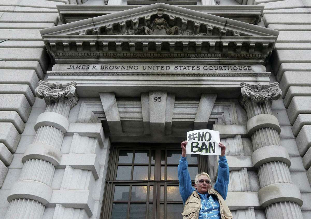 Karen Shore holds up a sign outside of the 9th U.S. Circuit Court of Appeals in San Francisco, Tuesday, Feb. 7, 2017. A panel of appeals court judges reviewing President Donald Trump's travel ban hammered away Tuesday at the federal government's arguments that the states cannot challenge the order.