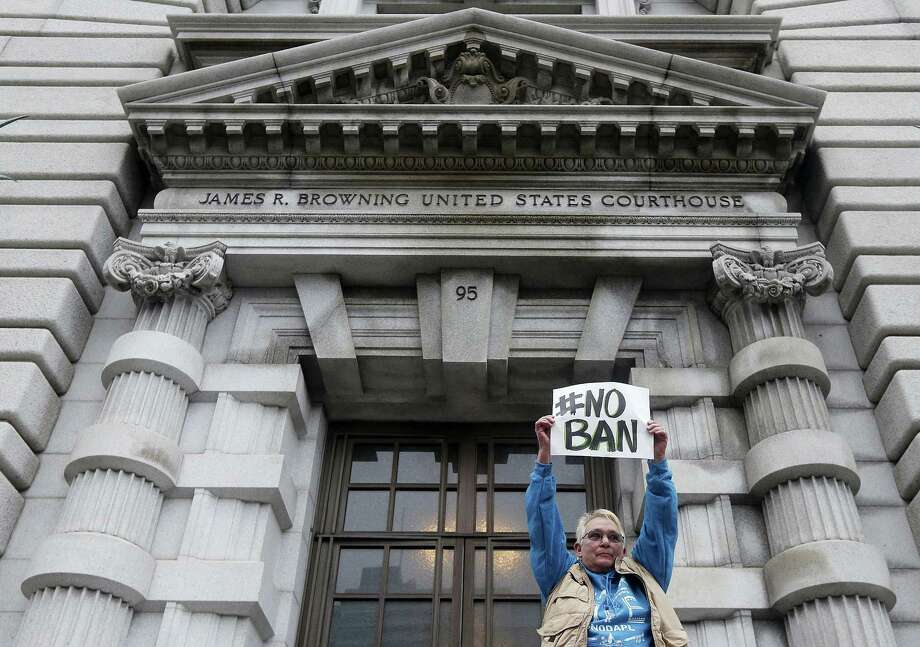 Karen Shore holds up a sign outside of the 9th U.S. Circuit Court of Appeals in San Francisco, Tuesday, Feb. 7, 2017. A panel of appeals court judges reviewing President Donald Trump's travel ban hammered away Tuesday at the federal government's arguments that the states cannot challenge the order. Photo: Jeff Chiu — AP Photo / Copyright 2017 The Associated Press. All rights reserved.
