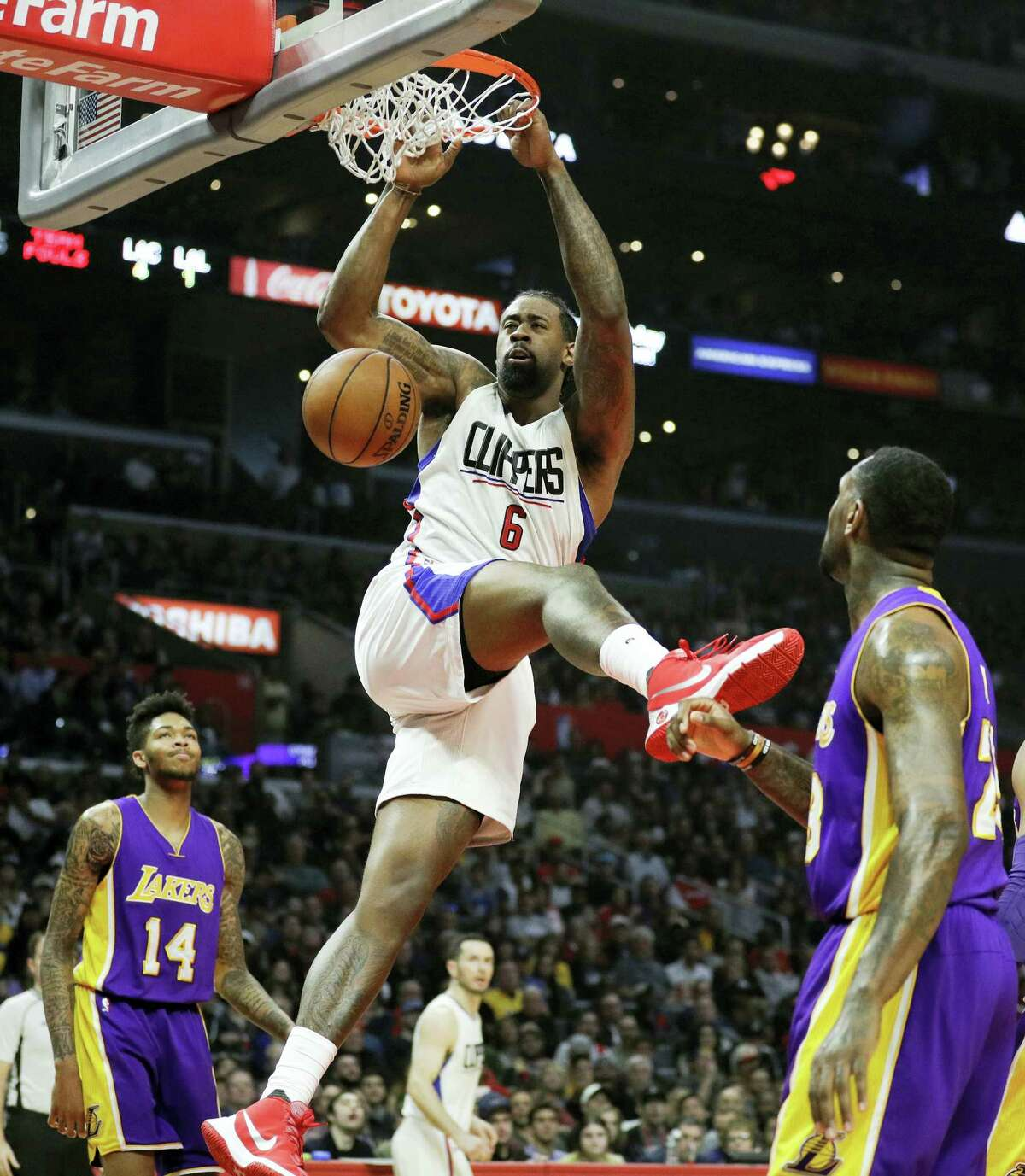 Los Angeles Clippers' DeAndre Jordan, center, dunks as Los Angeles Lakers' Brandon Ingram, background left, and Tarik Black watch during the first half of an NBA basketball game on Jan. 14, 2017 in Los Angeles.