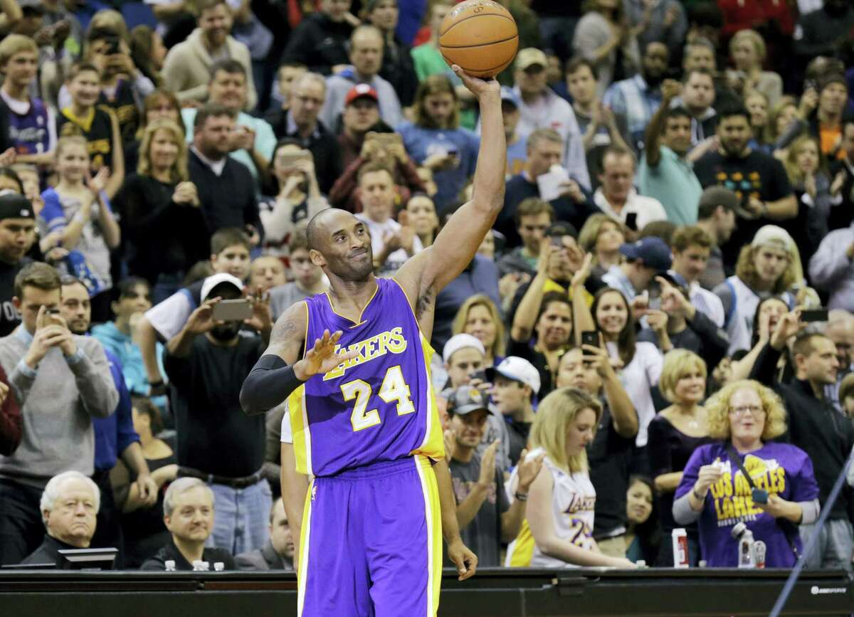 Los Angeles Lakers guard Kobe Bryant (24) holds up the game ball and acknowledges the crowd during the second quarter of an NBA basketball game against the Minnesota Timberwolves after passing Michael Jordan on the NBA all-time scoring list in Minneapolis on Sunday, Dec. 14, 2014.