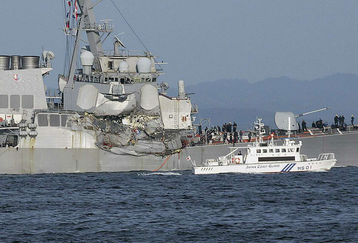 A Japan Coast Guard ship, foreground, navigates the damaged USS Fitzgerald near the U.S. Naval base in Yokosuka, southwest of Tokyo, after the U.S. destroyer collided with the Philippine-registered container ship ACX Crystal in the waters off the Izu Peninsula Saturday, June 17, 2017. The USS Fitzgerald was back at its home port in Japan after colliding before dawn Saturday with a container ship four times its size, while the coast guard and Japanese and U.S. military searched for seven sailors missing after the crash.