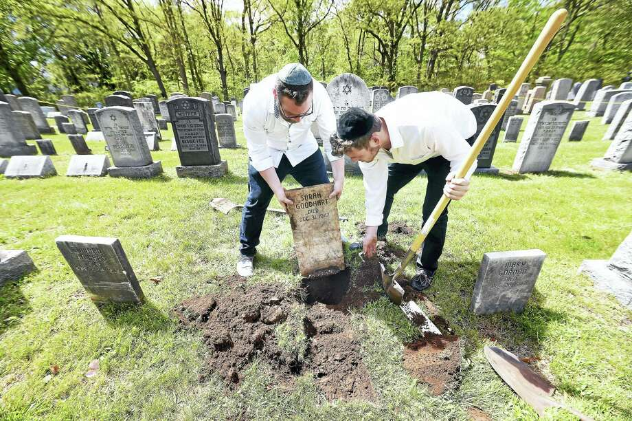 Eli Shuchatowitz, left, and Ari Weinstock of Yeshiva Meor Dovid in New Haven unearth a tombstone at the Hebrew Free Cemetery in East Haven Sunday during an event to repair, clean and map the cemetery. Photo: Arnold Gold — New Haven Register