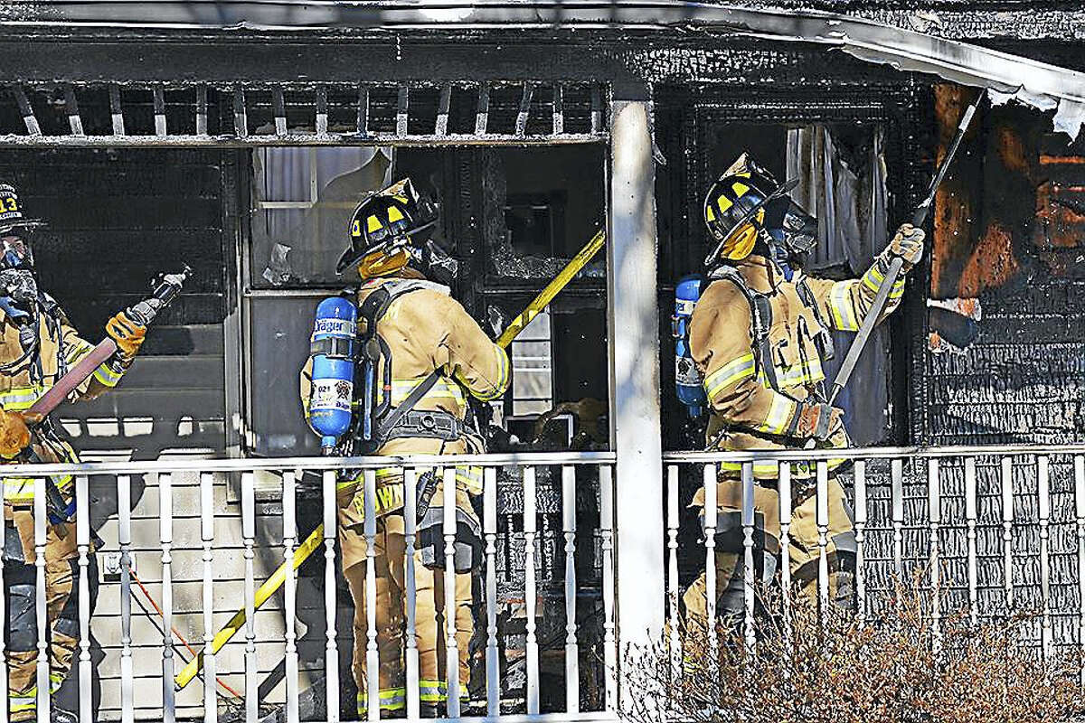 Haddam firefighters, who were aided by six other companies Monday morning, work to extinguish a blaze in the Higganum portion of town. Here, they vent the porch roof.