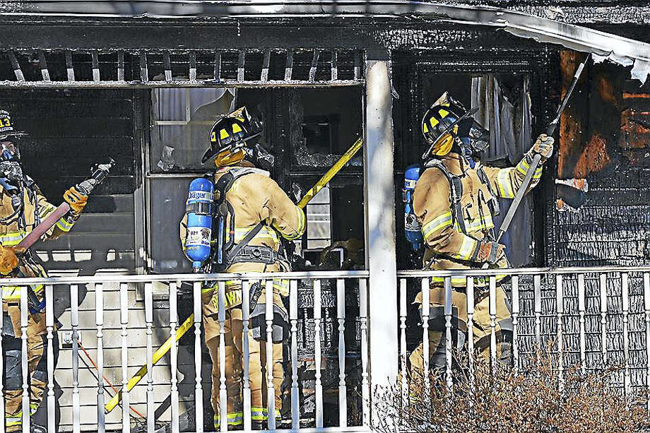 Haddam firefighters, who were aided by six other companies Monday morning, work to extinguish a blaze in the Higganum portion of town. Here, they vent the porch roof. Photo: Contributed Photo