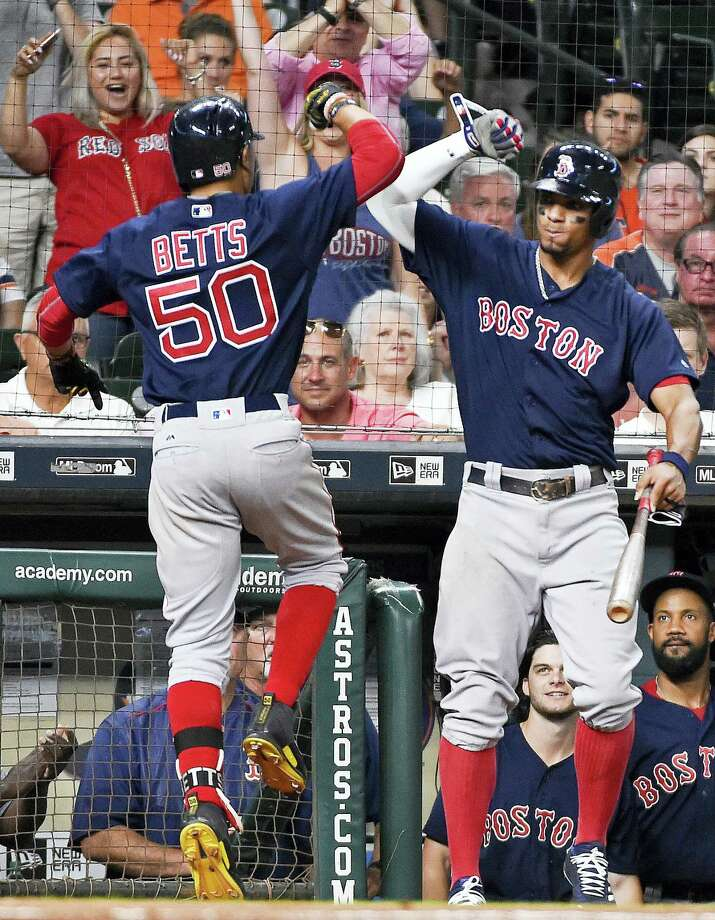 Mookie Betts (50) celebrates his go-ahead solo home run with Xander Bogaerts during the eighth inning Friday in Houston. Photo: Eric Christian Smith — The Associated Press  / FR171023 AP