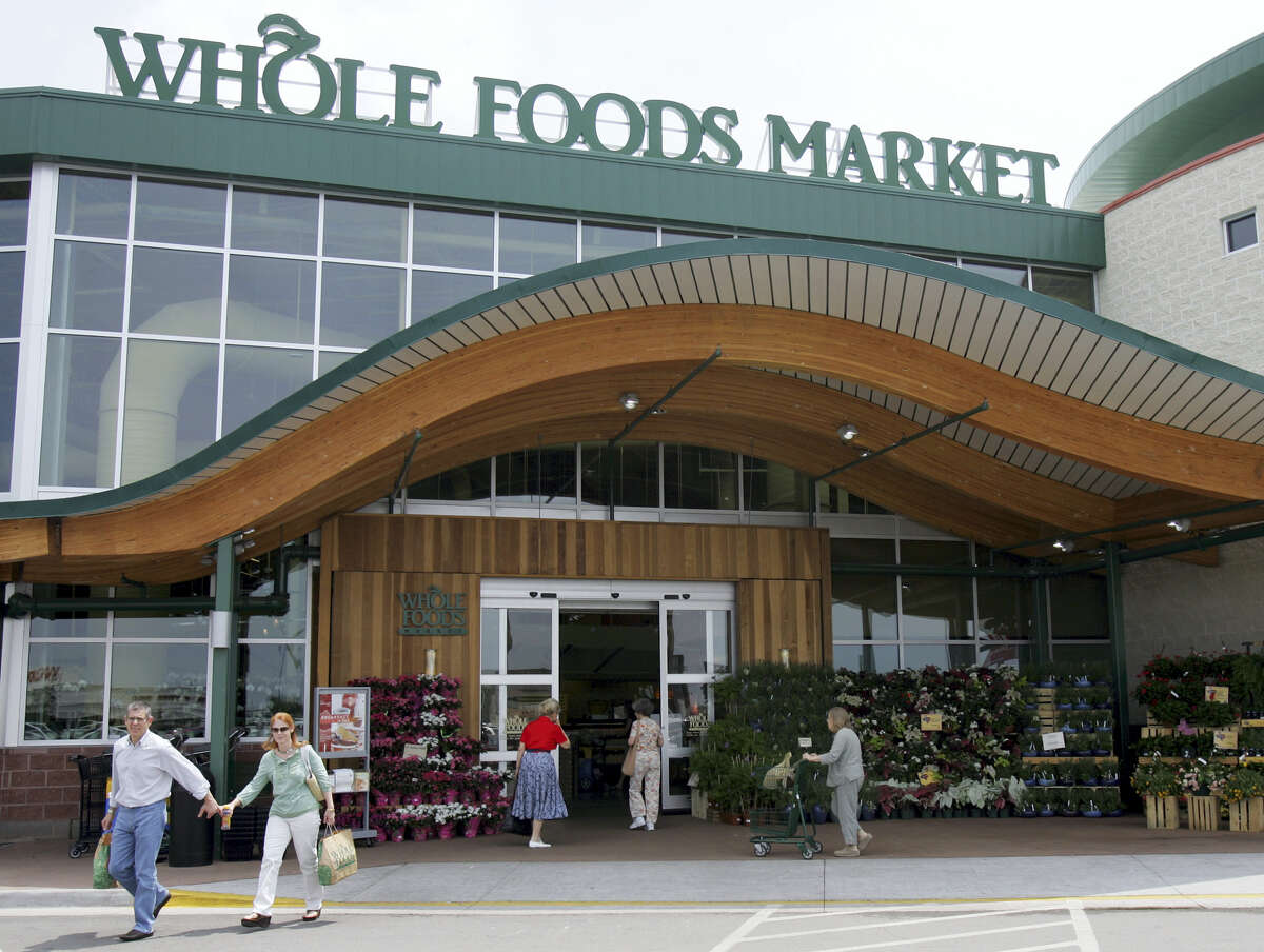 In this May 9, 2007, file photo, customers are seen outside a Whole Foods Market in Dallas. Online juggernaut Amazon announced Friday, June 16, 2017, that it is buying Whole Foods in a deal valued at about $13.7 billion, including debt. Amazon.com Inc. will pay $42 per share of Whole Foods Market Inc.