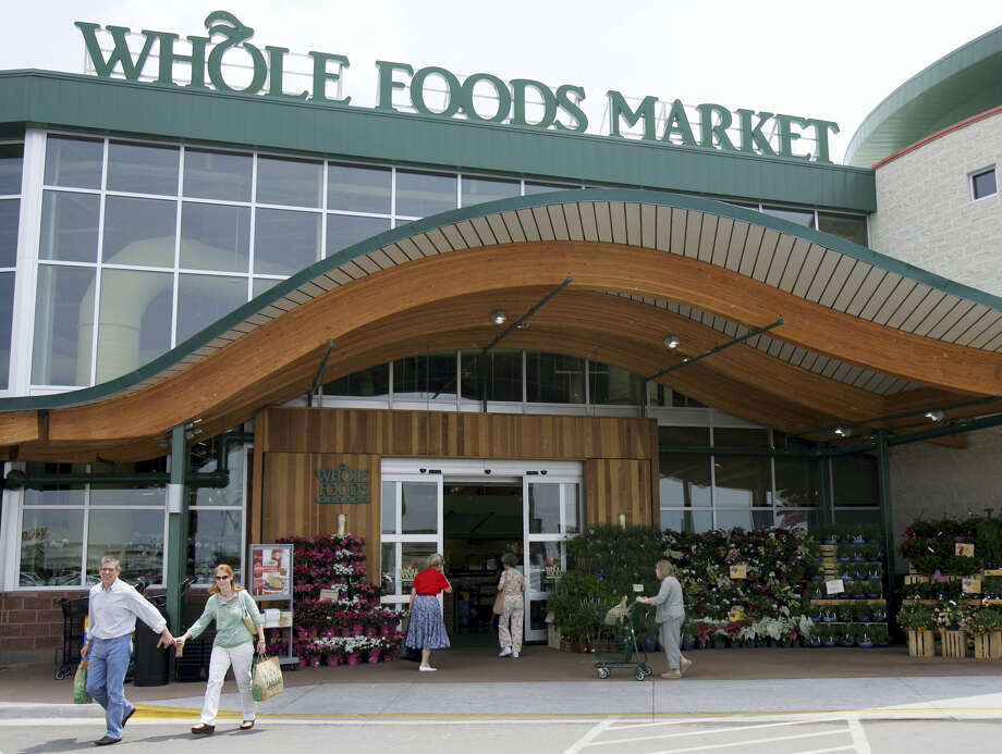 In this May 9, 2007, file photo, customers are seen outside a Whole Foods Market in Dallas.   Online juggernaut Amazon announced Friday, June 16, 2017, that it is buying Whole Foods in a deal valued at about $13.7 billion, including debt. Amazon.com Inc. will pay $42 per share of Whole Foods Market Inc. Photo: AP Photo/LM Otero, File   / Copyright 2017 The Associated Press. All rights reserved.