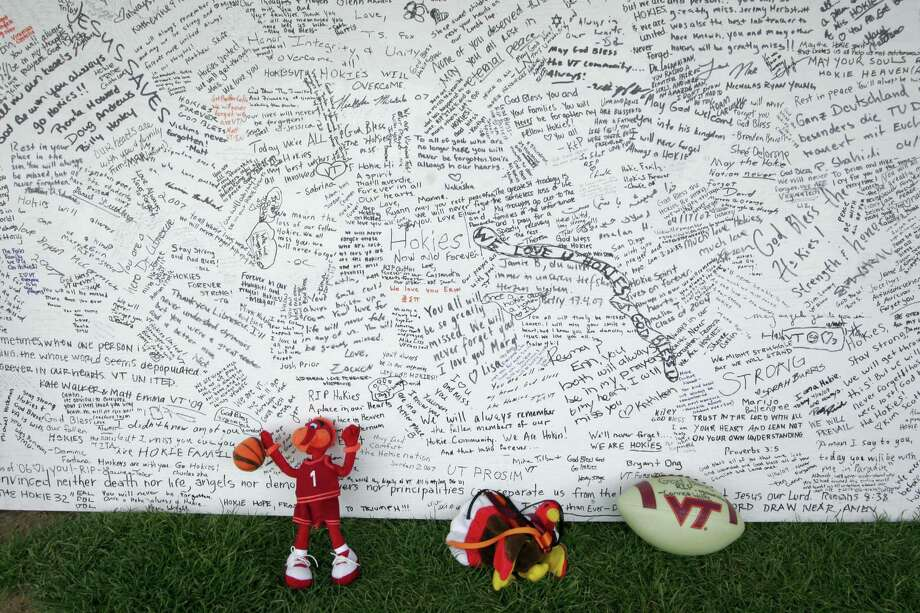 FILE - In this April 28, 2007 file photo, a memorial board sits under a tent with items that were placed in front of it, on the Drillfield on the Virginia Tech campus in Blacksburg, Va. Ten years after a mentally ill student fatally shot 32 people at Virginia Tech, survivors and families of the slain are returning to campus to honor the lives that were lost that day. Virginia Tech is holding a series of events Sunday, April 16, 2017 to mark the anniversary of the deadly campus shooting on April 16, 2007. (AP Photo/Alex Brandon, File) Photo: AP / Copyright 2017 The Associated Press. All rights reserved.
