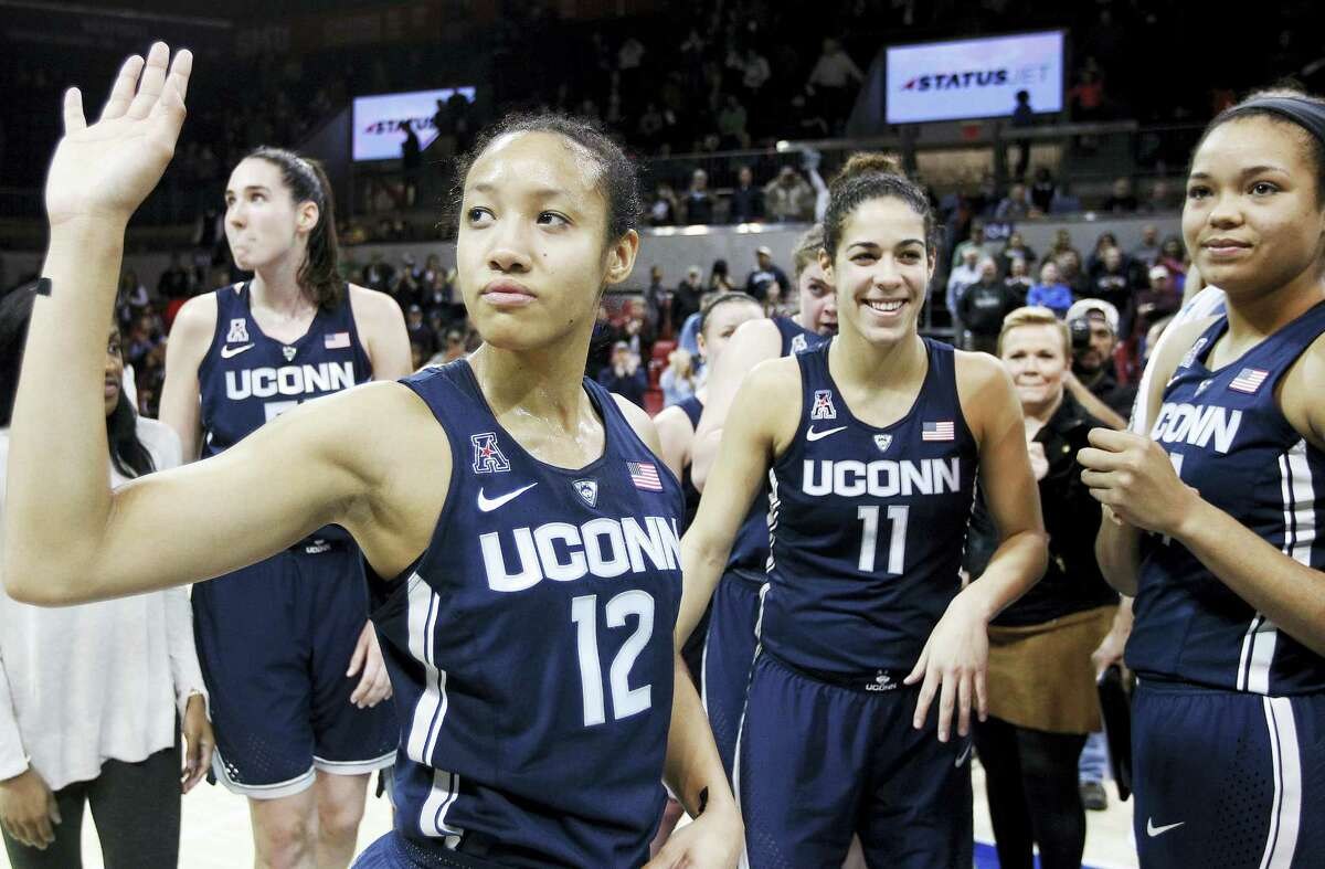 UConn's Saniya Chong (12) and her teammates wave to fans after beating SMU Saturday in Dallas for the Huskies' record 91st straight win.