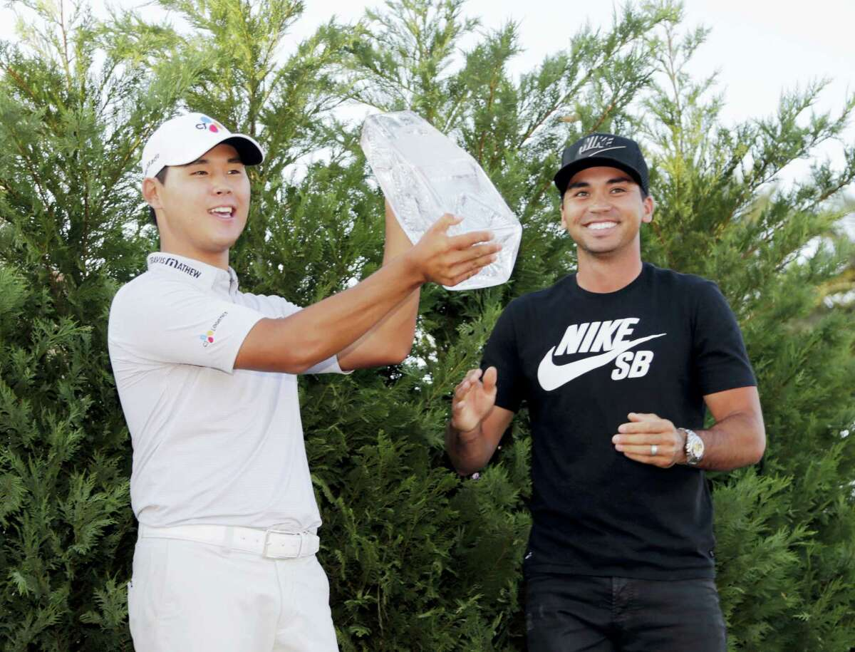 Si Woo Kim holds The Players Championship Trophy Sunday in Ponte Vedra Beach, Fla. To the right is Jason Day who won the tournament last year.