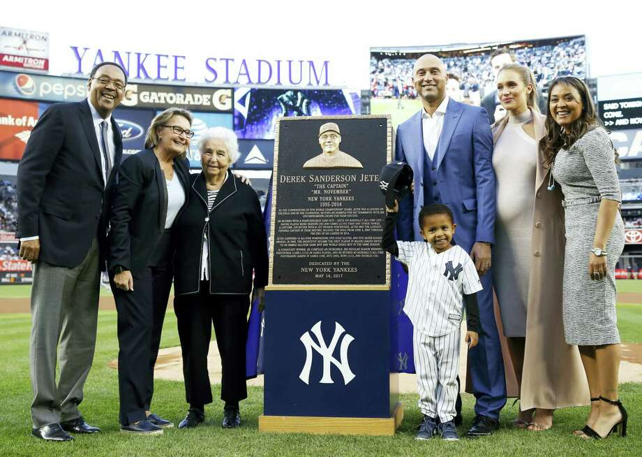 Retired Yankees shortstop Derek Jeter, third from right, poses with members of his family during a pregame ceremony retiring his No. 2 in Monument Park at Yankee Stadium on Sunday. Photo: Kathy Willens — The Associated Press  / Pool