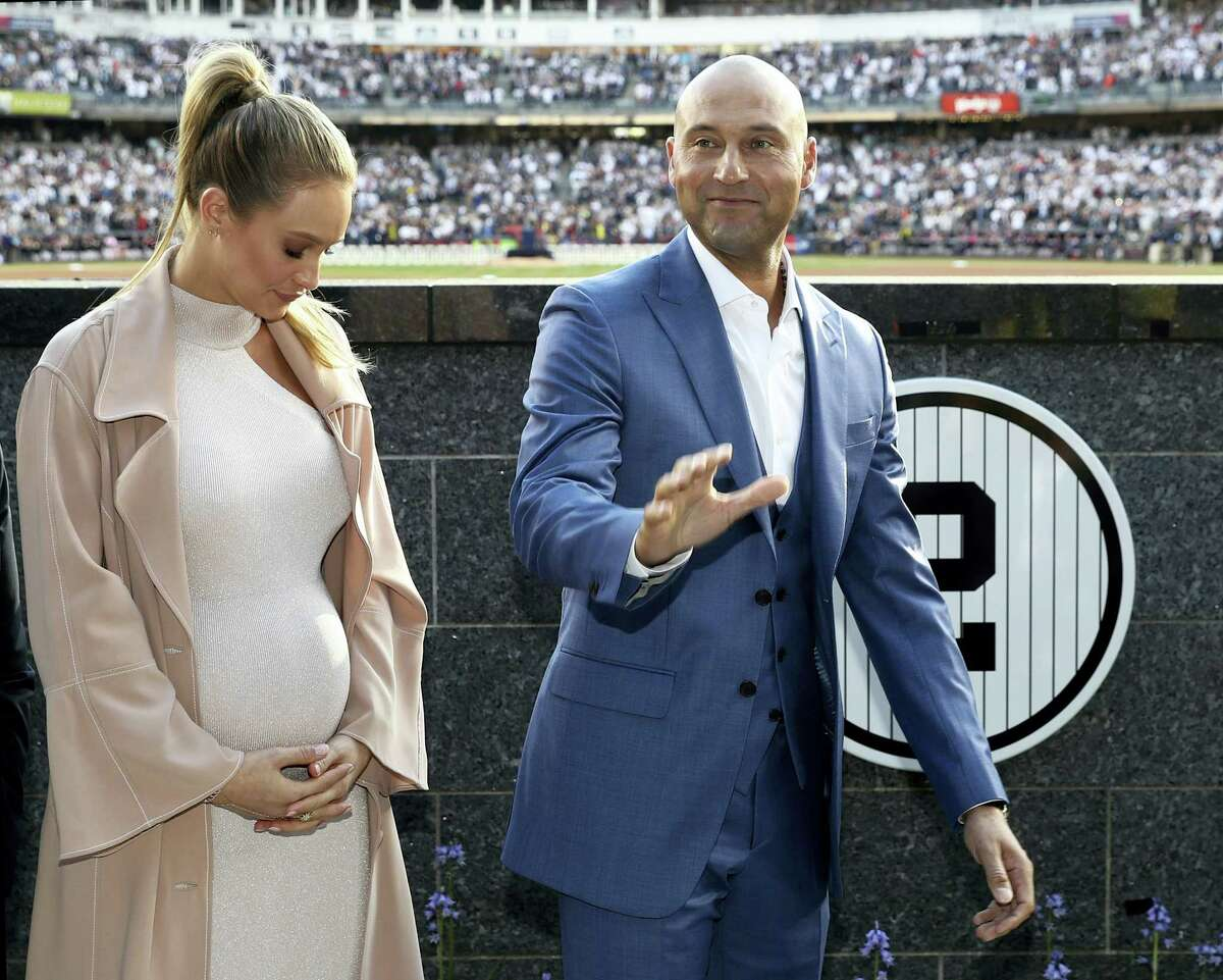 With his wife Hannah Jeter at his side, Derek Jeter waves during Sunday's pregame ceremony.