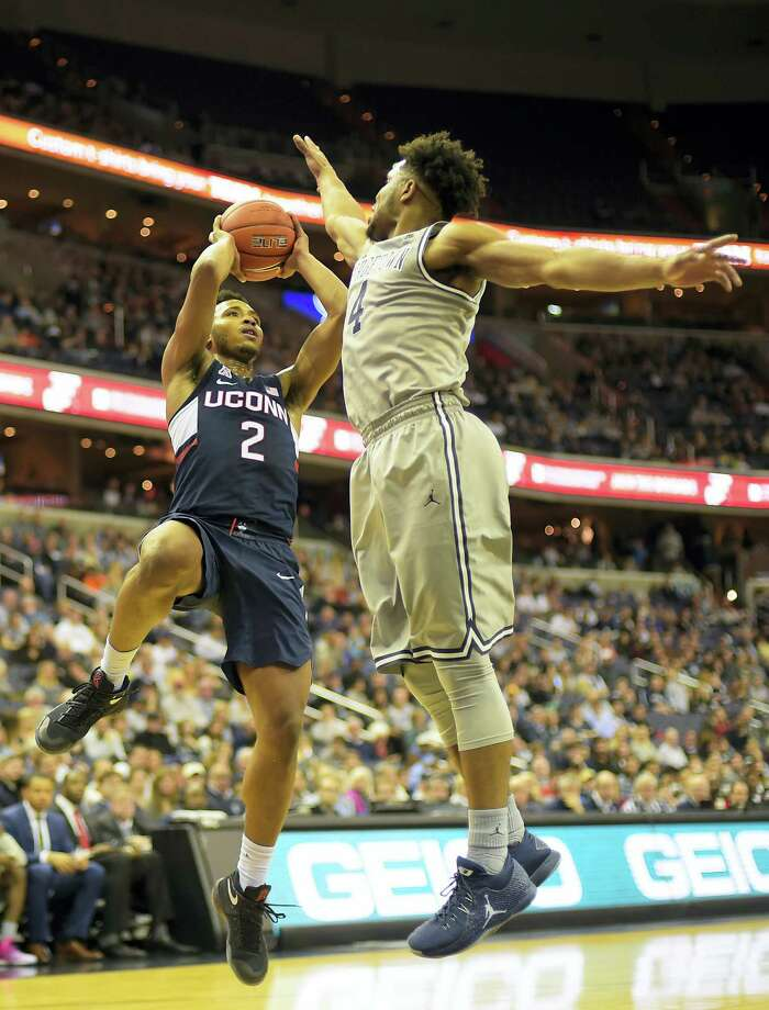 UConn's Jalen Adams, left, shoots against Georgetown's' Jagan Mosely during Saturday's game. Photo: John McDonnell — The Washington Post Via AP  / The Washington Post