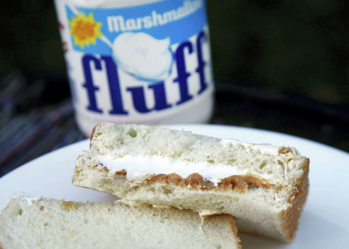In this Sept. 27, 2013 photo, a jar of Marshmallow Fluff and a Fluffernutter sandwich are displayed in North Andover, Mass. Archibald Query invented Fluff in 1917 in the Boston suburb of Somerville. The marshmallow concoction that's been smeared on a century's worth of sandwiches has inspired a festival and other sticky remembrances as it turns 100 in 2017.