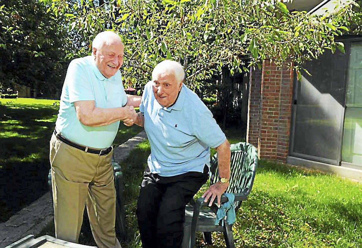 Ninety-five-year-old Sal Maniscalco, left, helps up his twin brother Tom as they hang out together at Sal's condo in Fairfield on Wednesday.