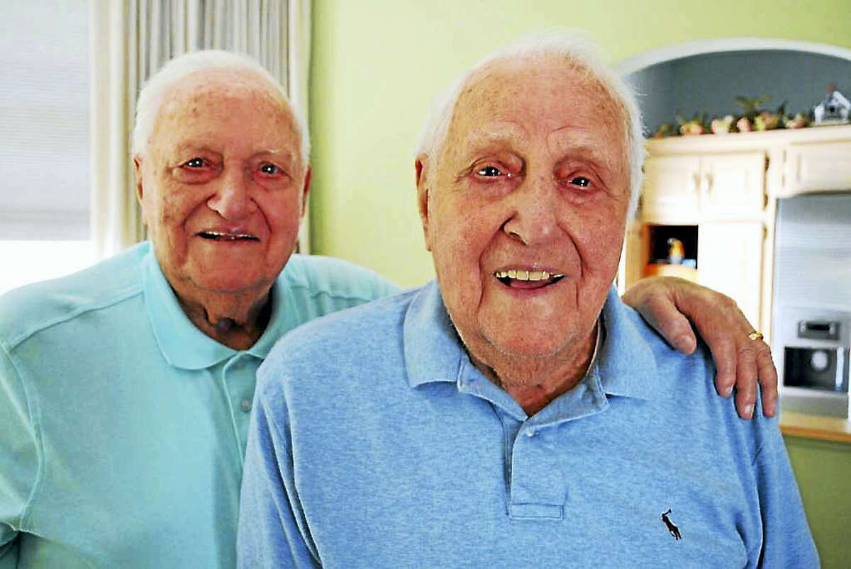 Ninety-five-year-old twins Sal and Tom Maniscalco, right, pose together at Sal's condo in Fairfield on Wednesday.