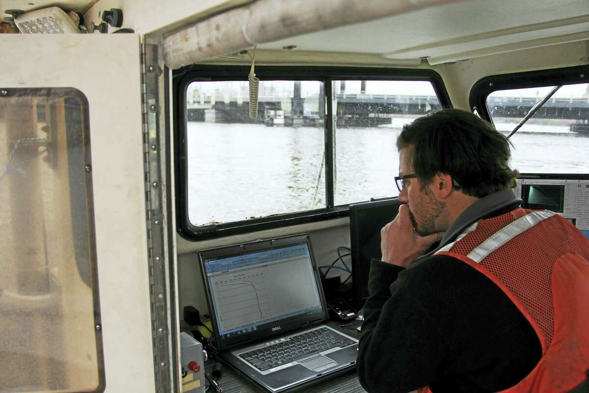 Anna Bisaro — New Haven Register Jeff Pydeski of Ocean Surveys looks over data gathered during a survey on a small boat in Bridgeport Harbor. There are three canal barges underwater in the harbor.