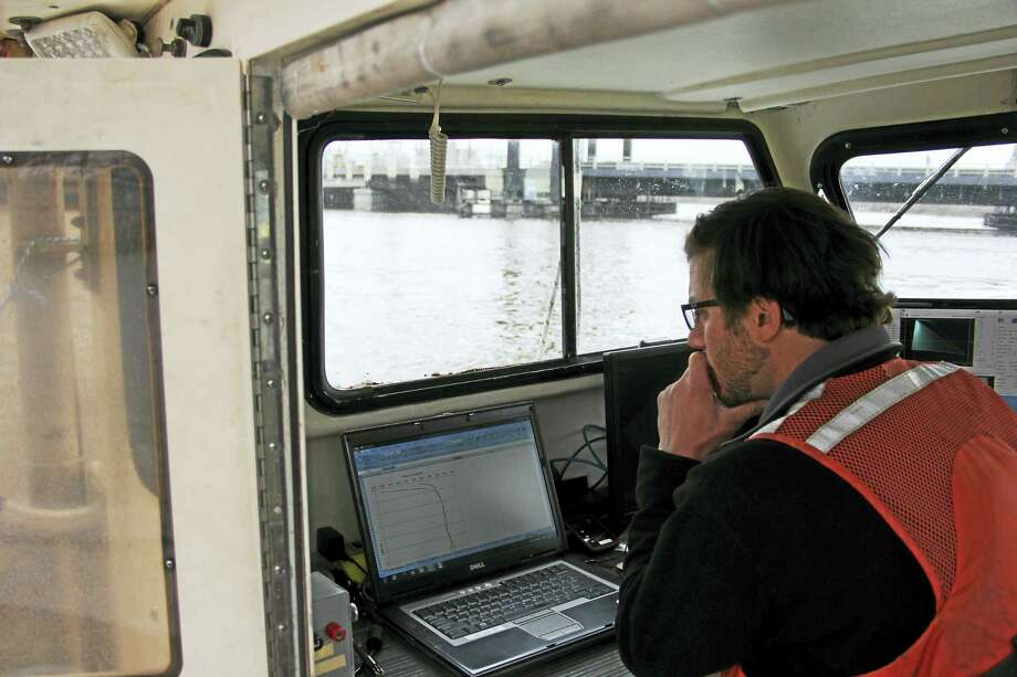 Anna Bisaro — New Haven Register  Jeff Pydeski of Ocean Surveys looks over data gathered during a survey on a small boat in Bridgeport Harbor. There are three canal barges underwater in the harbor. Photo: Digital First Media