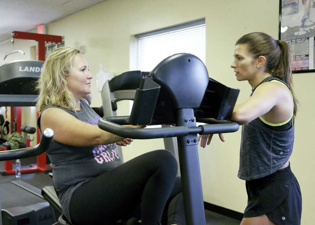 Associated Press writer Jenna Fryer, left, talks with Danica Patrick after a workout at Daytona International Speedway.