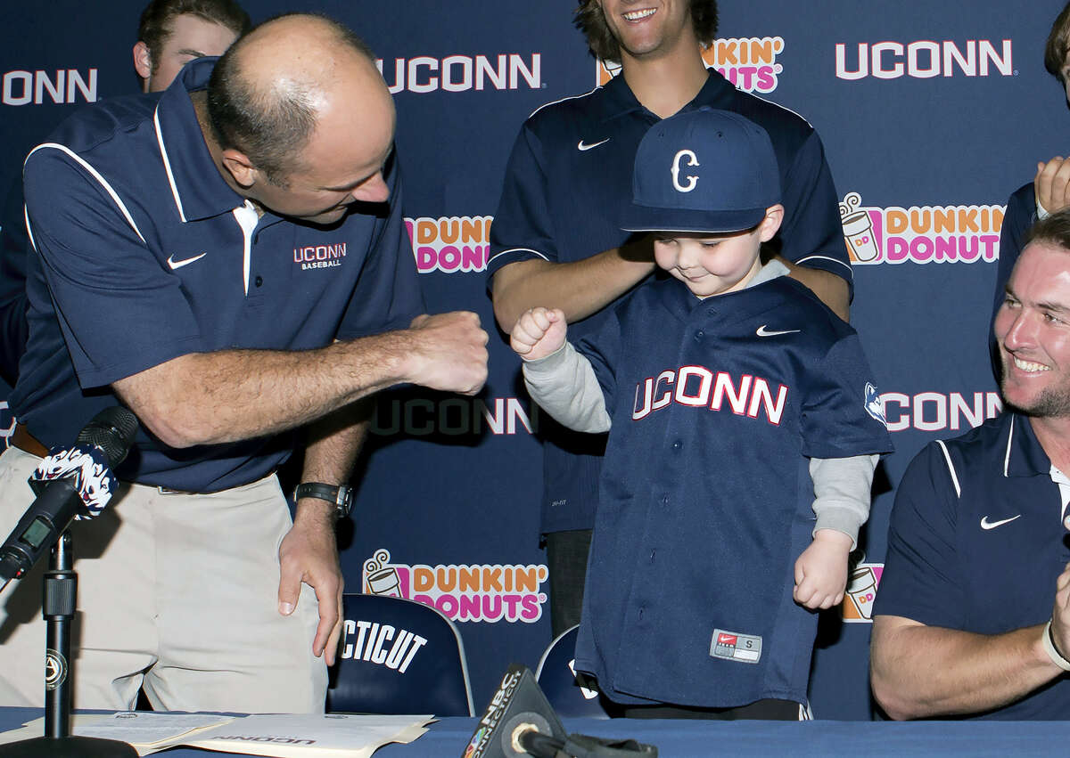 In this April 20, 2015 photo released by the University of Connecticut, leukemia patient Grayson Hand, center, bumps fists with UConn baseball coach Jim Penders, left, at a ceremony where he signed an honorary national letter of intent to become part of the UConn baseball team in Storrs. Hand has formed a special bond with UConn pitcher Ryan Radue, who was diagnosed with cancer later in 2015.