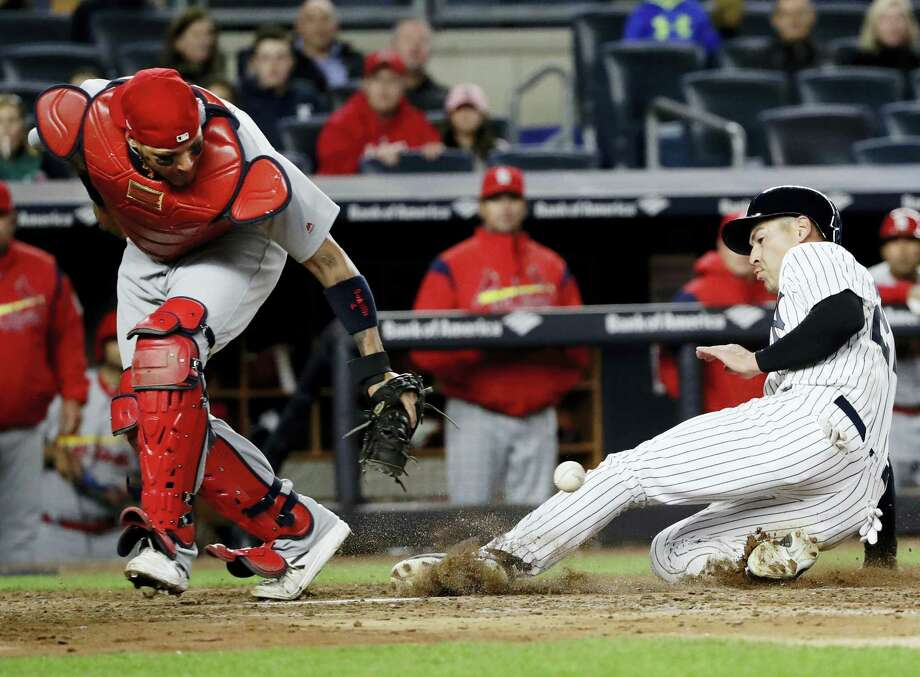 The Yankees' Jacoby Ellsbury, right, scores on a throwing error by the Cardinals' Kolten Wong in the fifth inning Friday in New York. Photo: Frank Franklin II — The Associated Press  / Copyright 2017 The Associated Press. All rights reserved.