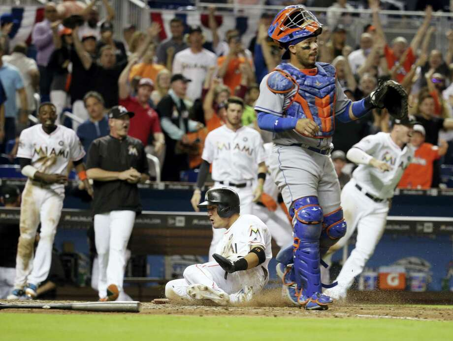 The Marlins' Miguel Rojas, center, scores the winning run on a double hit by J.T. Realmuto in the ninth inning Friday. Photo: Lynne Sladky — The Associated Press  / Copyright 2017 The Associated Press. All rights reserved.
