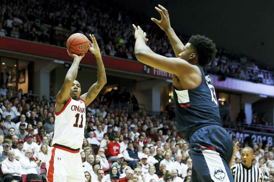 Cincinnati's Gary Clark, left, shoots over UConn's Steven Enoch in the first half Saturday. Photo: John Minchillo — The Associated Press  / AP