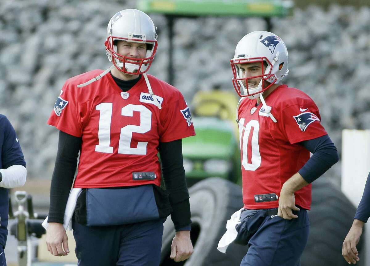 Patriots quarterbacks Tom Brady (12) and Jimmy Garoppolo (10) speak while warming up during a recent practice