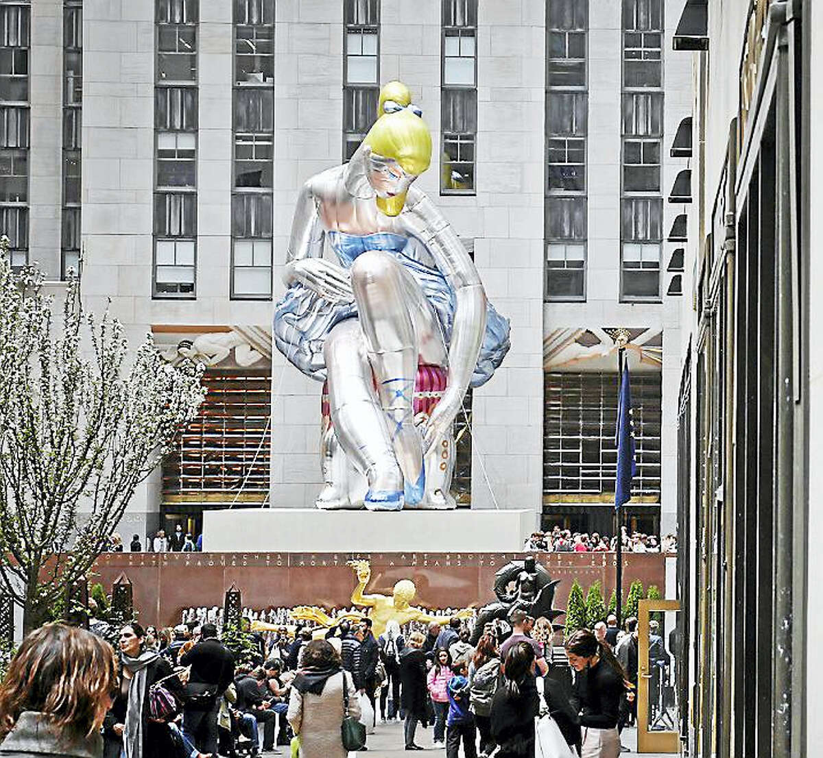 """""""Seated Ballerina"""", center, the public art exhibition of a 45-foot inflatable nylon sculpture depicting a seated ballerina from artist Jeff Koons' Antiquity series, is displayed at Rockefeller Center in New York City after it was unveiled Friday May 12, 2017."""