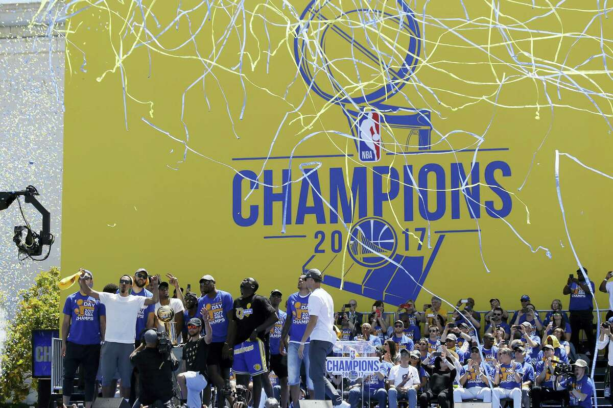 The Golden State Warriors celebrate at the conclusion of their NBA championship rally Thursday in Oakland.
