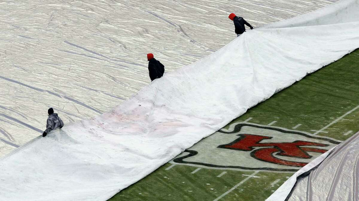 In this file photo, grounds crew members remove the tarp from the playing field in Kansas City.