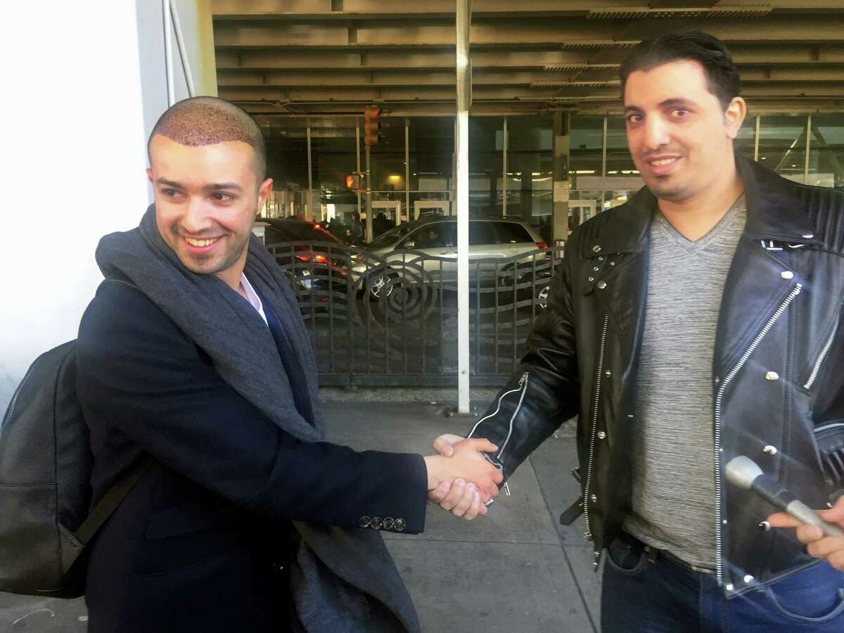 Ammar Alnajjar, left, shakes hands with his cousin, Fahd Alfakih, after coming into New York's JFK International Airport on a flight from Istanbul, Turkey, Saturday, Feb. 4, 2017. The government on Saturday suspended enforcement of President Donald Trump's refugee and immigration ban, enabling Alnajjar to return from Turkey where he was visiting his wife.