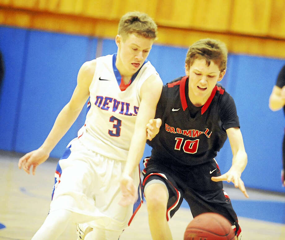 Coginchaug's Ryan Cross, left, and Cromwell's Noah Budzik fight for a loose ball in the Blue Devils' 58-45 win Friday. Photo: Jimmy Zanor - The Middletown Press