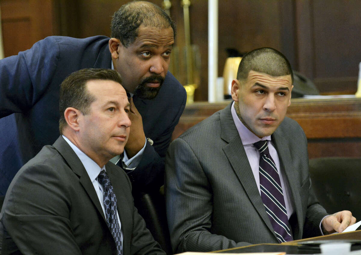 From left, lead defense attorney Jose Baez, defense attorney Ronald Sullivan and Aaron Hernandez listen to Judge Jeffrey Locke during a hearing requesting a continuance Friday in Boston for Hernandez' upcoming double murder trial.