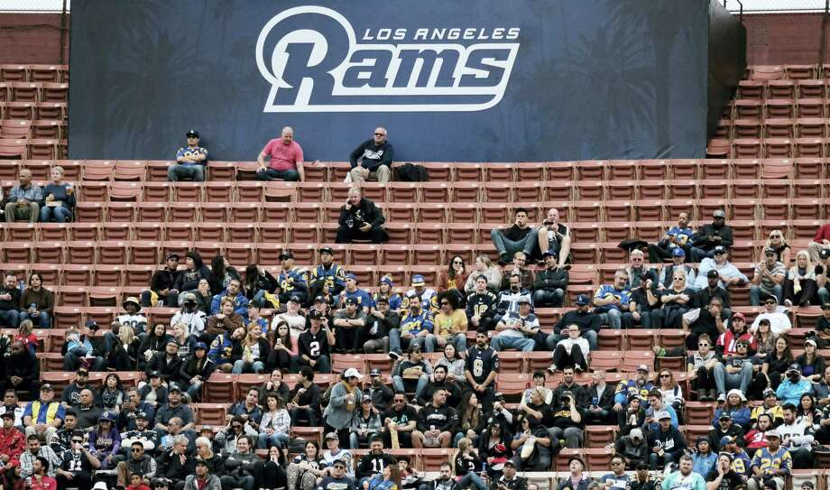 Surrounded by empty seats, Los Angeles Rams fans watch their team play the Atlanta Falcons. TV ratings declined 8 percent, with the presidential election partly, but not solely, to blame. Many of the league's highest-profile contests were boring blowouts, including eight of the 10 playoff games leading to Sunday's Super Bowl between the Patriots and Falcons. Photo: The Associated Press File Photo  / Copyright 2016 The Associated Press. All rights reserved.