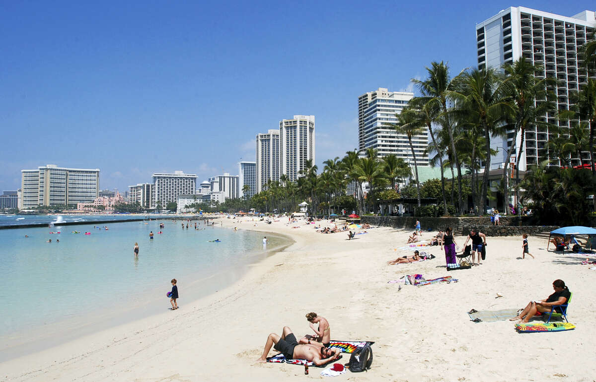 In this March 13 photo, people relax on the beach in Waikiki in Honolulu. Many Americans might dream of going on vacation to places such as Waikiki, but a new poll shows nearly half of Americans won't be taking a summer vacation this year, mostly because they can't afford it and some because they can't get away from work.