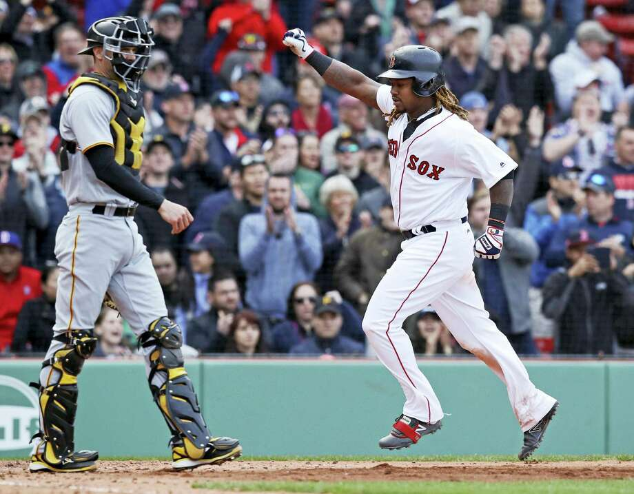 Hanley Ramirez, right, pumps his fist as he passes Pirates catcher Chris Stewart while scoring on an RBI single by Xander Bogaerts during the eighth inning Thursday. Photo: Charles Krupa — The Associated Press  / Copyright 2017 The Associated Press. All rights reserved.