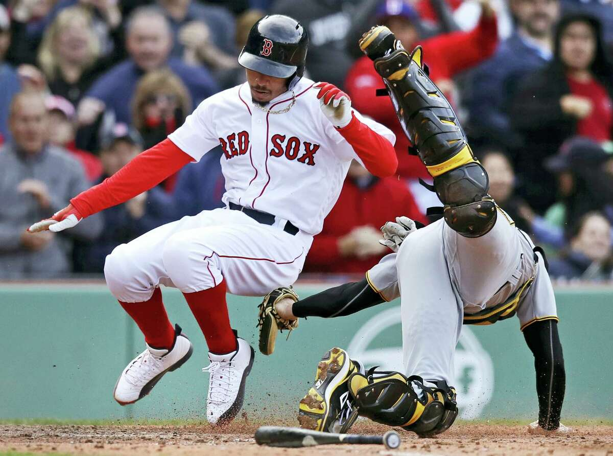 Pittsburgh Pirates catcher Chris Stewart, right, tags out Boston Red Sox's Mookie Betts while trying to score during the eighth inning Thursday.