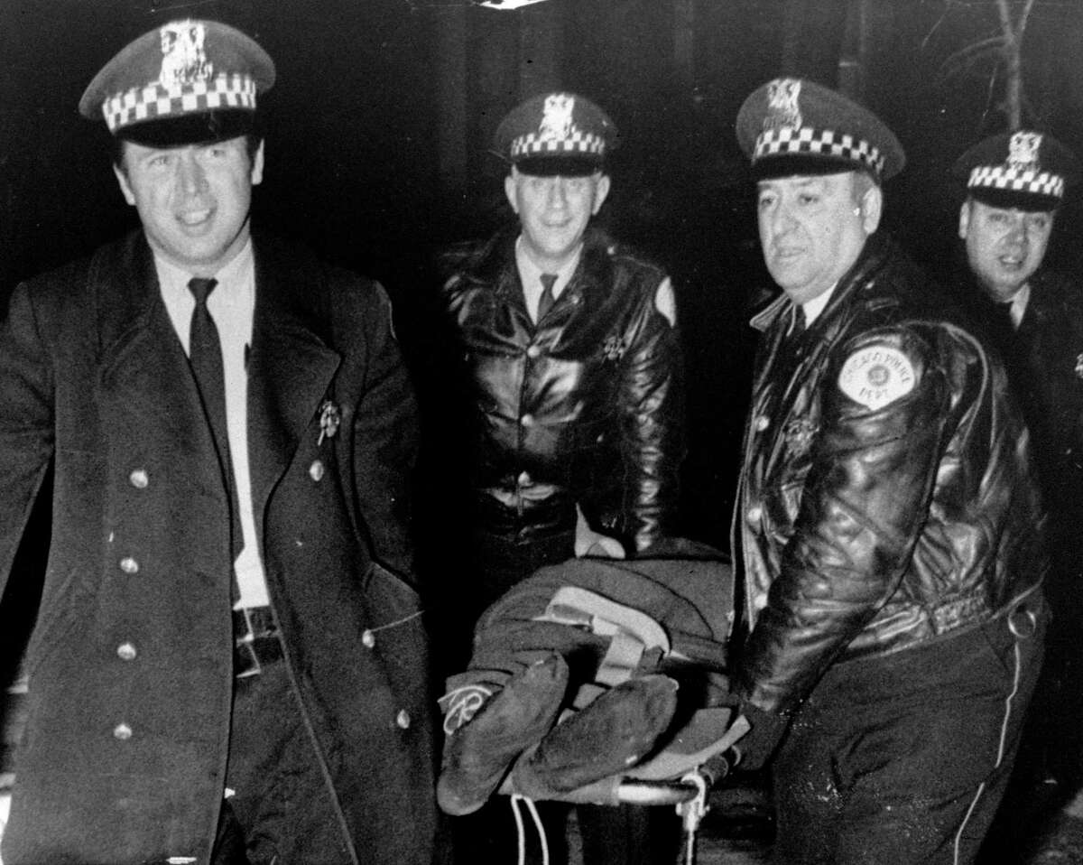 In this Dec. 4, 1969, file photo, Chicago police remove the body of Fred Hampton, leader of the Illinois Black Panther party, who was slain in a gun battle with police on Chicago's west side. The U.S. Justice Department on Friday, Jan. 13, 2017, is scheduled to release the findings of an investigation of the Chicago Police Department, and a law enforcement official says the report will show a pattern of civil rights violations. The probe was launched after a video showed a white officer fatally shooting a black teenager 16 times.