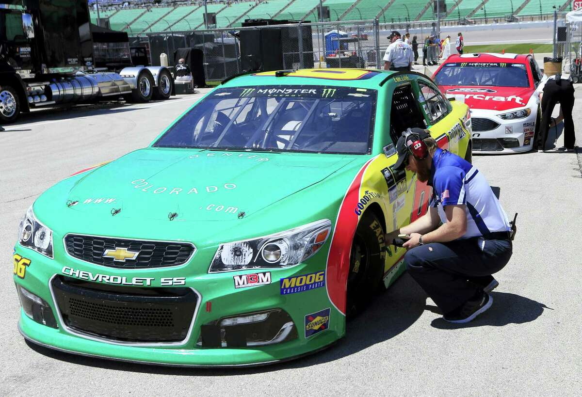 Driver Carl Long get his tires checked during practice at Kansas Speedway on Friday.