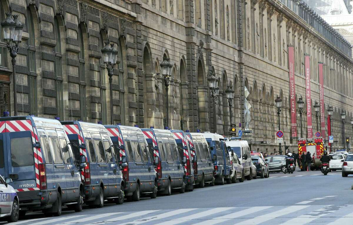 Police vehicles are parked-up outside the Louvre museum near where a soldier opened fire after he was attacked in Paris, Friday, Feb. 3, 2017. Police say the soldier opened fire outside the Louvre Museum after he was attacked by someone, and the area is being evacuated.