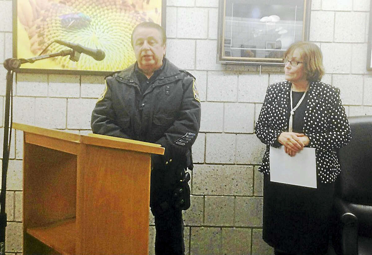 Portland Police Lt. Milardo and First Selectman Susan Bransfield, right, speak during the Board of Selectmen's recognition of officers who helped apprehend the suspect in Tuesday night's armed robbery of the Tri-Town Foods grocery story on Route 66.