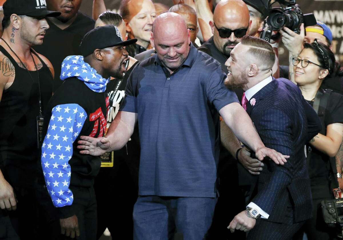 UFC president Dana White, center, intervenes as boxer Floyd Mayweather Jr., left, and mixed martial arts fighter Conor McGregor exchange words during a news conference Tuesday in Los Angeles.