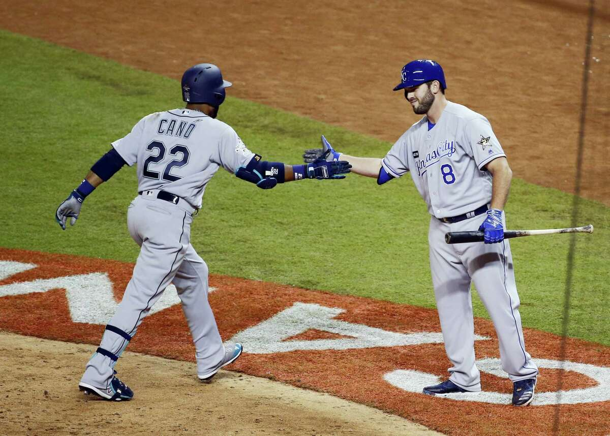 Robinson Cano (22) is congratulated by Mike Moustakas, after Cano hit a home run in the 10th inning.
