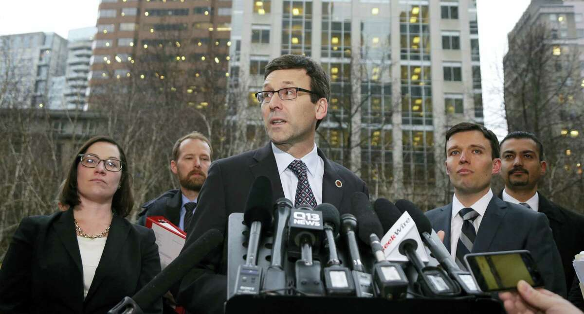 Washington Attorney General Bob Ferguson, center, talks to reporters as Solicitor General Noah Purcell, second from right, looks on, Friday, Feb. 3, 2017, following a hearing in federal court in Seattle. A U.S. judge on Friday temporarily blocked President Donald Trump's ban on people from seven predominantly Muslim countries from entering the United States after Washington state and Minnesota urged a nationwide hold on the executive order that has launched legal battles across the country.