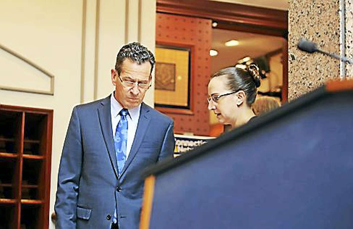 Gov. Dannel P. Malloy confers with his communications director, Kelly Donnelly, before walking to the podium.