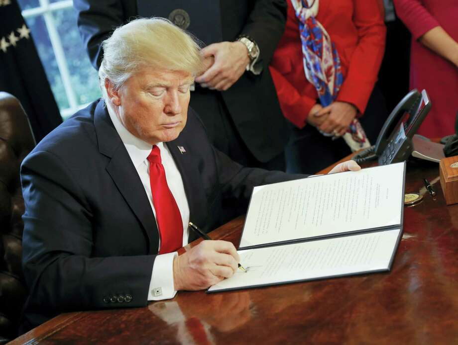 President Donald Trump signs an executive order in the Oval Office of the White House in Washington, Friday. Trump signed an executive order that will direct the Treasury secretary to review the 2010 Dodd-Frank financial oversight law, which reshaped financial regulation after 2008-2009 crisis. Photo: Pablo Martinez Monsivais — The Associated Press  / Copyright 2017 The Associated Press. All rights reserved.