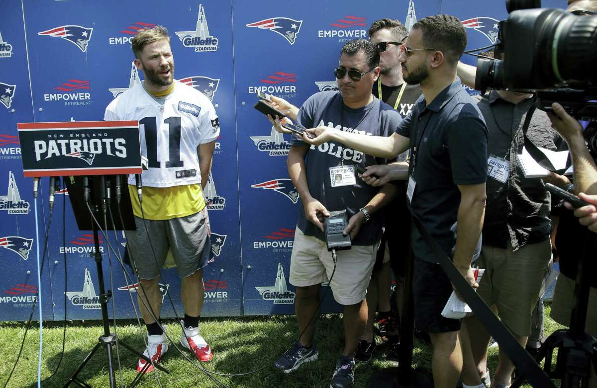 New England Patriots wide receiver Julian Edelman, left, speaks with members of the media following NFL football practice, on Tuesday in Foxborough, Mass.
